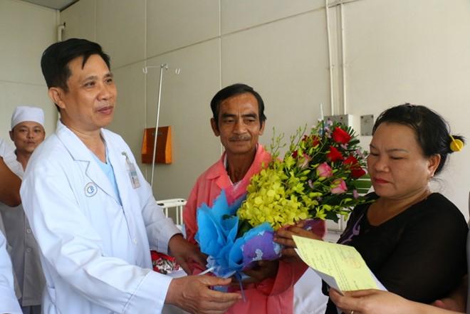Lãnh đạo Bệnh viện Chợ Rẫy tặng hoa chúc mừng ông Nén được xuất viện. Ảnh: Bệnh viện cung cấp.