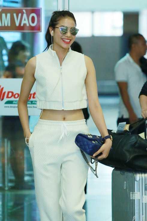 Hoa hậu Hoàn vũ Việt Nam 2015 diện bộ trang phục màu trắng năng động, khoe vòng eo thon.Cô xách túi Chanel, đeo kính tráng gương sành điệu và đi giày thể thao.