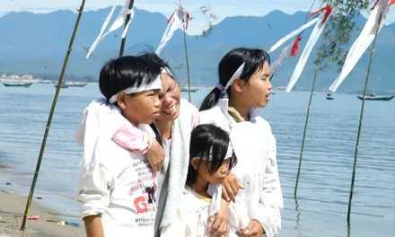 Mẹ và con nạn nhân xấu số tại lễ cầu siêu cho linh hồn các nạn nhân xấu số 10 năm trước. Ảnh T.Tuấn.