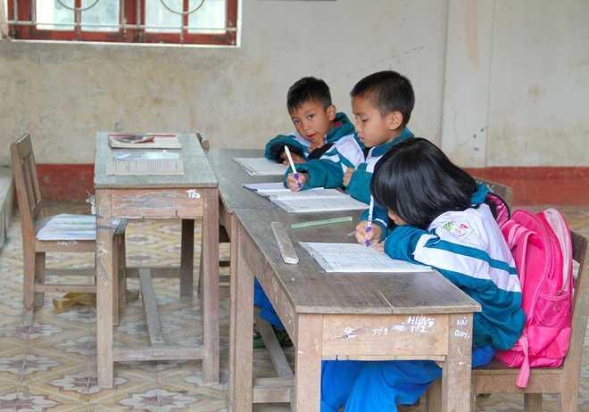 Vì mỗi lớp có 3 học sinh nên bàn ghế được bố trí đơn sơ, cô giáo cũng sắp xếp chỗ ngồi của mình ngay cạnh các em để tiện dạy dỗ.