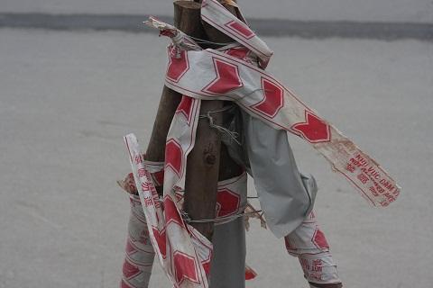 Ba que củi khô dùng làm chân đỡ, những vòng dây ni lông cùng dây thép lỏng lẻo quấn lấy nhau nham nhở.