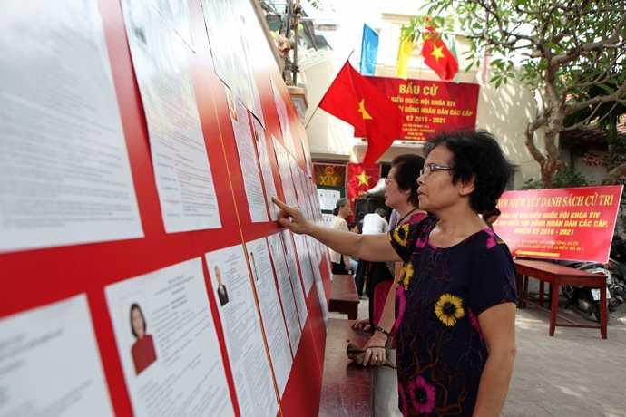 Người dân xem danh sách những người ứng cử tại đơn vị bầu cử số 3, phường Bưởi, quận Tây Hồ, Hà Nội (Ảnh: Baogiaothong)