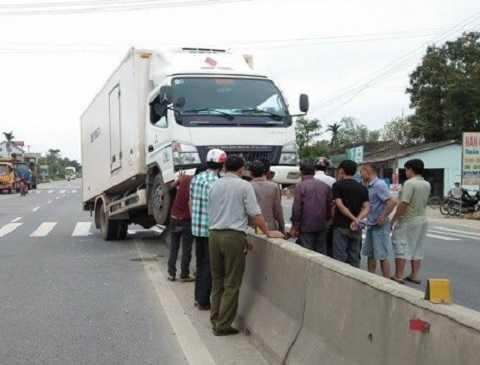 Tài xế và người dân đang tìm cách đưa xe mắc kẹt ra ngoài