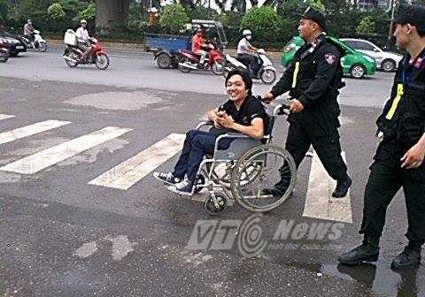 Lực lượng an ninh đưa khách mời là người khuyết tật vào TTHNQG (Ảnh: Phạm Thịnh)