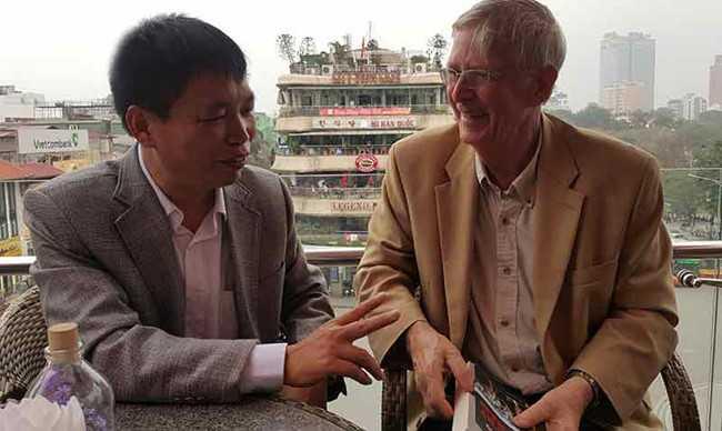 Nhà văn Đặng Vương Hưng tặng hoa ông Carl W. Greifzu (bên phải) và hai người thân mật trò chuyện