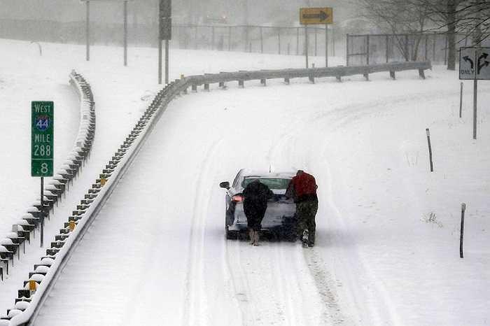 2 người đẩy chiếc xe trên con đường đầy tuyết ở St. Louis, Mỹ