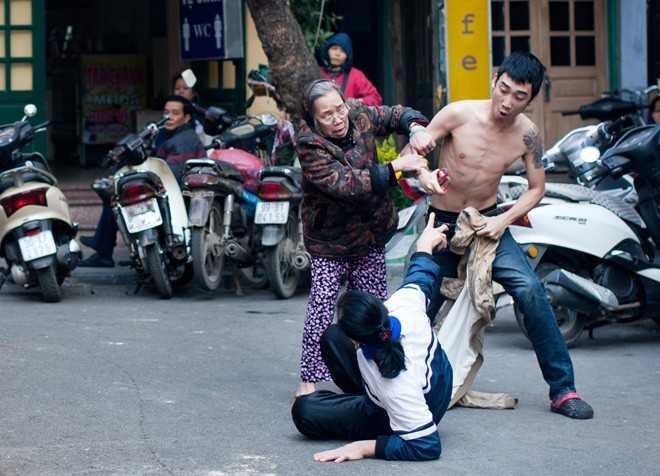 Giữa lòng đường, gần khu vực chợ Hàng Bè, mặc cho thanh niên cởi trần cầm kéo đâm một phụ nữ lớn tuổi, người dân hai bên vỉa hè chỉ dám ngồi xem. Chỉ có một cụ bà chạy tới can ngăn.