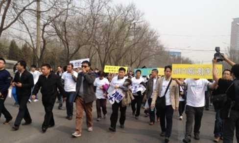 Người nhà các hành khách của MH370 biểu tình trên đường tới đại sứ quán Malaysia ở Bắc Kinh (Nguồn: Guardian)