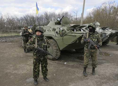 Binh lính Ukraine được hộ tống bởi xe bọc thép đứng gác ở trạm kiểm soát gần thị trấn Izium