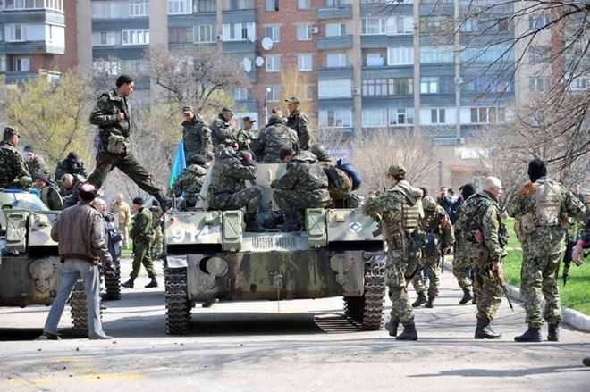 Xe bọc thép của một nhóm vũ trang chưa rõ thuộc lực lượng nào trấn giữ bên ngoài một tòa nhà chính quyền ở thành phố Slavyansk
