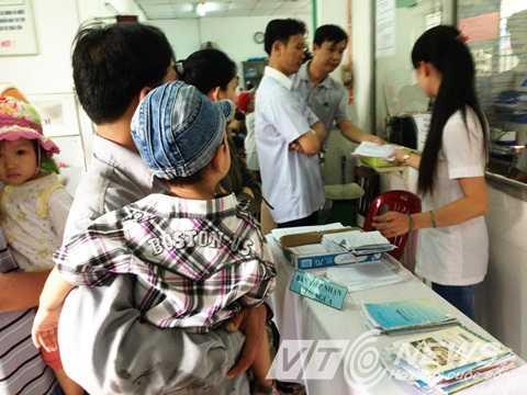 Đến trưa 21/4, đông đảo phụ huynh vẫn ngồi chờ trước khu vực trạm y tế quận Thủ Đức