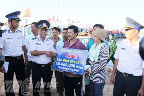 Đại tá Trần Văn Dũng, chính ủy Cảnh sát biển Vùng 2 tặng quà cho chủ tàu cá ĐNa 90152