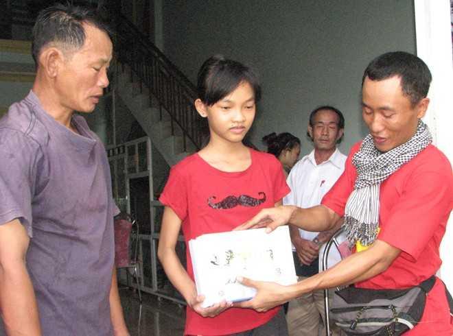 õ Mạnh Tuấn (ngoài cùng bên phải) trao quà cho em Lê Thị Đào Duyên (học sinh lớp 9 trường THCS Lý Tự Trọng, trú phường Thọ Quang, quận Sơn Trà, Đà Nẵng).