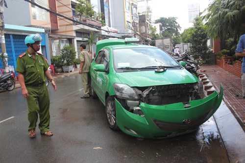 Phần mui xe taxi bị hư hỏng nặng, lốp bên trái xe bị nổ tung