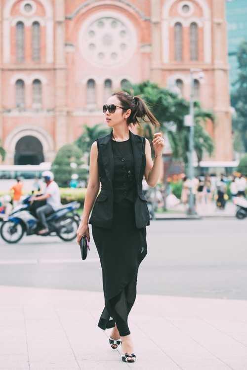 Vì muốn thay đổi hình ảnh, Hoa hậu đã nhờ nhà thiết kế may              riêng cho bộ đồ đen cá tính. Trang phục kết hợpáo blazer không tay với              quần váy xuyên thấu.