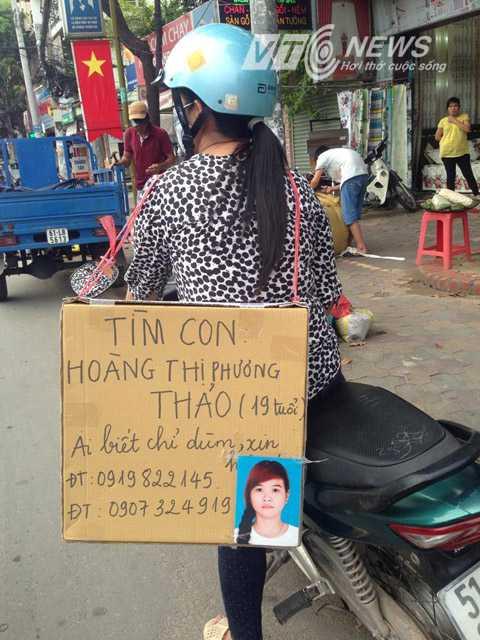 Chị L. đeo bảng tìm con gái khắp TPHCM. Ảnh: Huy Phan