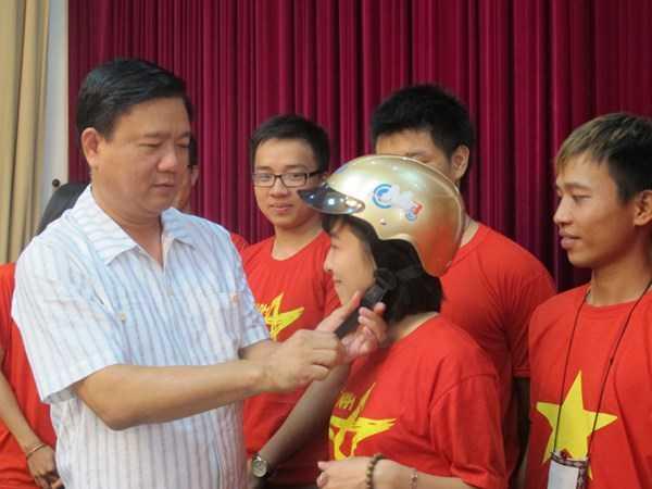 Bộ trưởng Đinh La Thăng trao mũ bảo hiểm cho các thành viên của nhóm phượt Phong Vân.