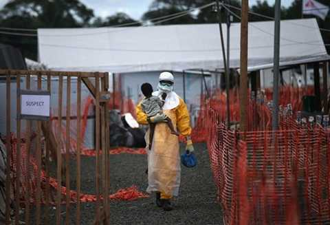 Một nhân viên y tế bế bé trai nhiễm Ebola đi vào trung tâm điều tị tại Liberia