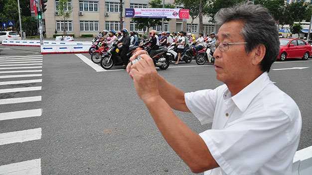 Ông Saito Takeshi, 69 tuổi, đến từ Saitama Urawa, Nhật Bản, đếm xe qua   lại ngay đầu cầu sông Hàn, TP Đà Nẵng để nghiên cứu về giao thông