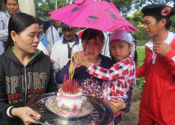 Bé Nguyễn Thị Cẩm Huyền, con chị Ngọc, cùng mọi người đưa quan tài mẹ ra huyệt mộ - Ảnh: Đ.Vịnh