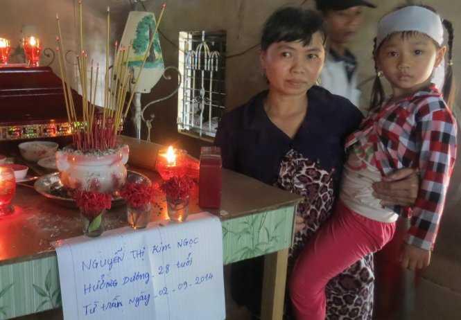 Bé Nguyễn Thị Cẩm Huyền, con chị Ngọc, bên bàn thờ mẹ - Ảnh: Đ.Vịnh