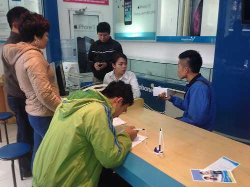 Anh Hiếu (ngoài cùng bên phải) là khách hàng đầu tiên sở hữu iPhone 6 tại cửa hàng VinaPhone Huỳnh Thúc Kháng (Hà Nội) khi xếp hàng từ 7h tối ngày 13/11