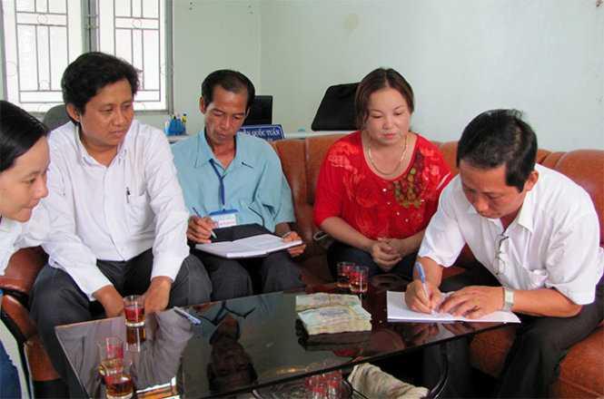 Hiệu trưởng các trường nhận tiền tại trụ sở UBND xã Vĩnh Lộc A về chia sẻ khó khăn cho giáo viên trường mình vào chiều 14/11 - Ảnh: Ngọc Anh
