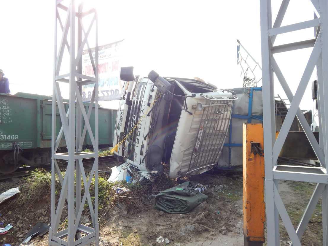 Chiếc xe tải bị hất tung, nằm sát đường ray. (Ảnh: Bình An)