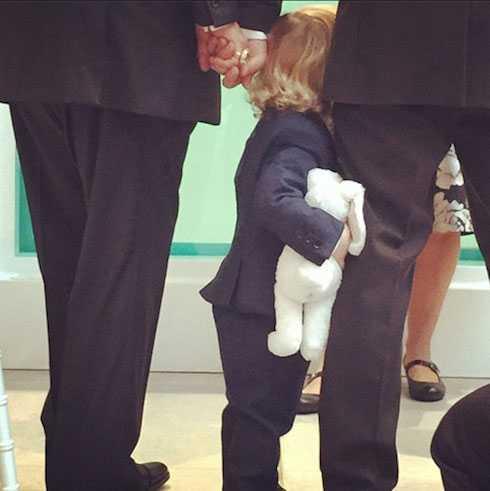 Cậu con trai út của danh ca đang bám chân bố khi hai ông bố nắm chặt tay nhau.