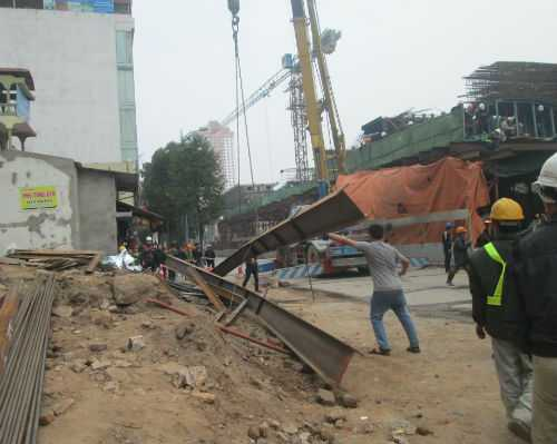 Thanh sắt nặng hàng tấn đè lên chiếc taxi đã bị bẻ cong.