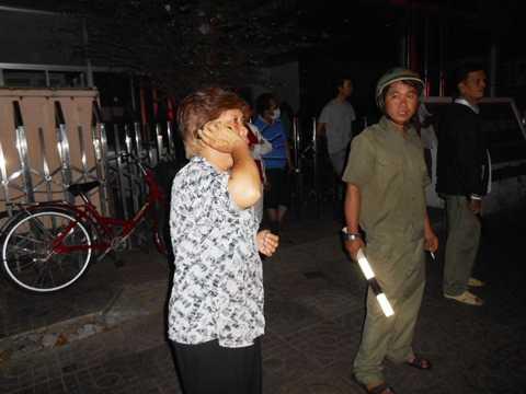 Một người dân hốt hoảng điện thoại liên lạc với người thân đang có mặt trong đám cháy. Ảnh: Phan Cường
