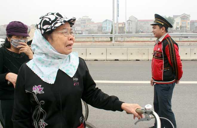 Cụ bà bật khóc vì không được đi xe đạp qua cầu Nhật Tân - Ảnh: VNE