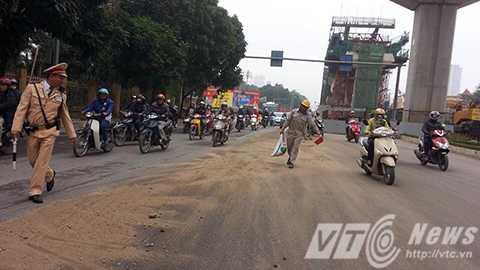 Lực lượng CSGT cùng công nhân phối hợp làm sạch mặt đường