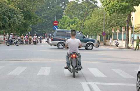 Một thanh niên không đội mũ bảo hiểm, chạy xe không biển số, vượt đèn đỏ trước mặt công an trên một con phố Hà Nội - Ảnh: Việt Dũng