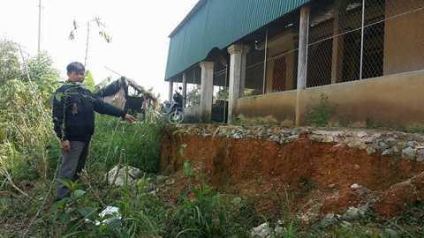 Hộ dân Nguyễn Tiến An đang chỉ vào điểm sạt lở đã sát móng nhà, sự cố này xuất hiện kể từ khi thi công kênh Ngàn Trươi. Hiện đang hoang mang vì lo trôi mất nhà.
