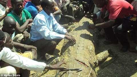 Anh Mubarak và người dân làng bên xác của con cá sấu. (Nguồn: Daily Mail)