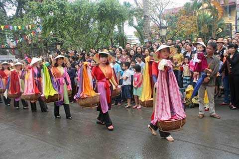 Những cô gái trẻ quẩy quang gánh chở lụa trên vai.