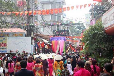 Những người phụ nữ trong làng diện áo dài, đội nón đi theo xe rước lụa.