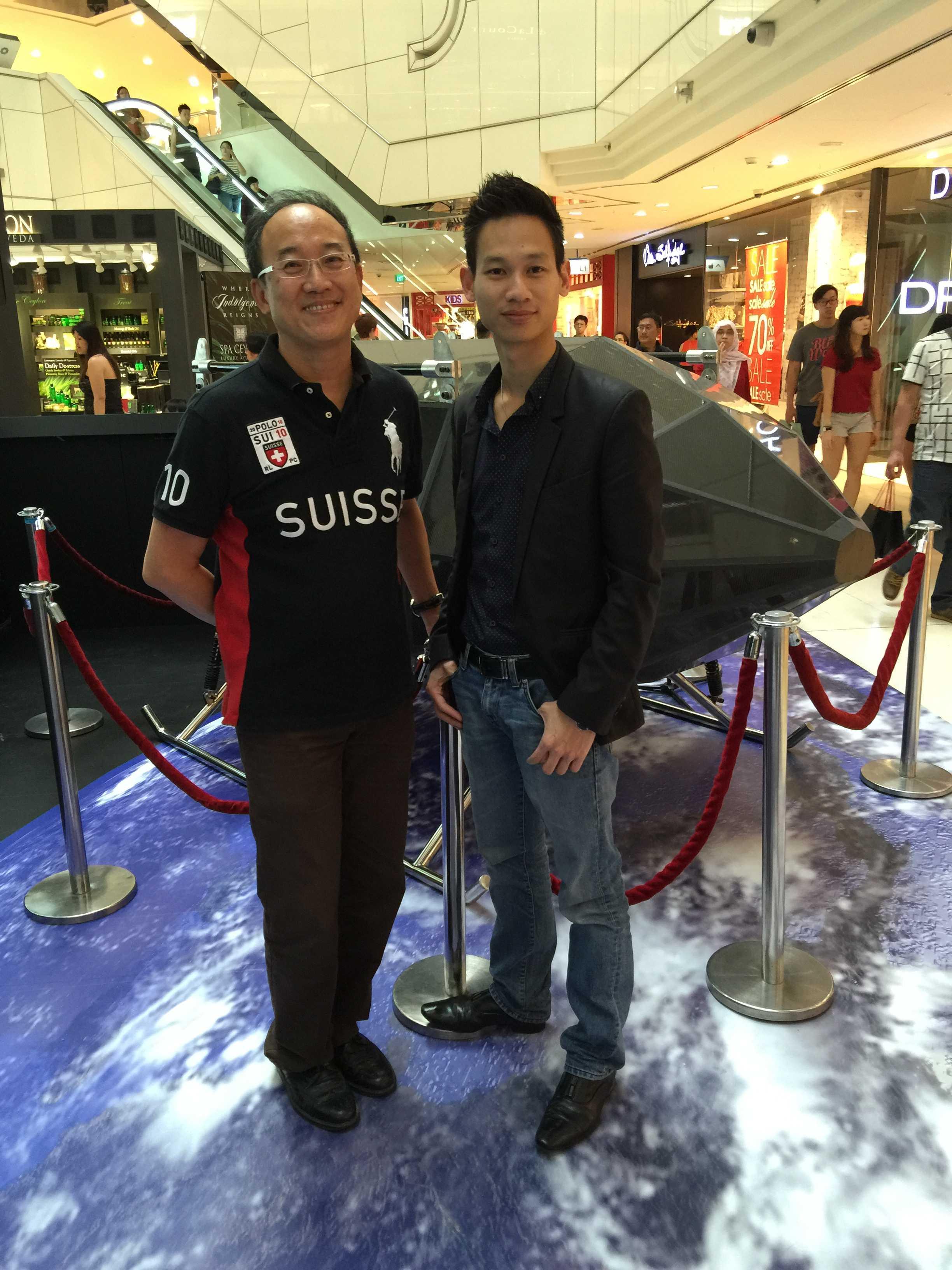Anh Phạm Gia Vinh (bên phải) bên thiết bị của mình tại Singapore
