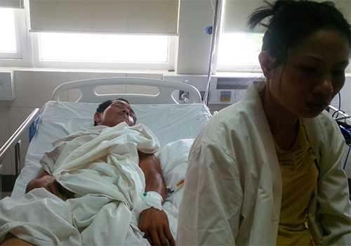 Ông Nguyễn Gia Hải, tài xế xe ben, được vợ chăm sóc tại Phòng Hồi sức sau phẫu thuật tại Bệnh viện Quốc tế Huế. Ảnh: Đắc Đức.