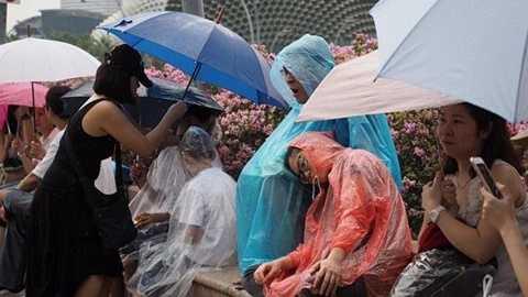 Người dân chờ đợi đám tang ông Lý Quang Diệu đi ngang trên đường phố dưới trời mưa to từ sáng sớm ngày 29/3 - Ảnh: Stratstimes