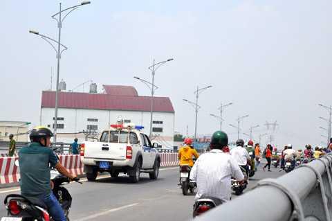 Công nhân băng bộ trên cầu vượt, xe cảnh sát dừng lại cảnh báo các phương tiện khác. Ảnh: Phan Cường