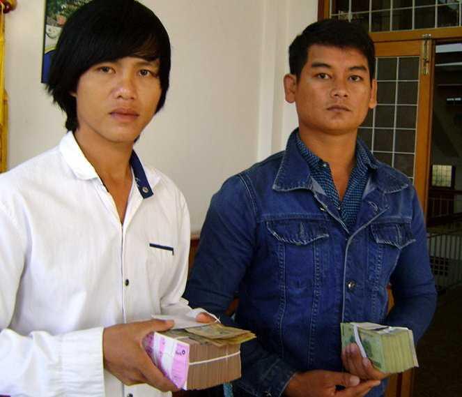 Trần Văn Đỡ (trái) người bị điều tra viên còng tay treo lên cửa sổ để ép cung và Khâu Sóc nhận tiền bồi thường sau khi được minh oan - Ảnh: Phương Nguyên