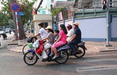 Nhiều phụ huynh học sinh chưa chấp hành cho con em mình đội mũ bảo hiểm khi ra đường