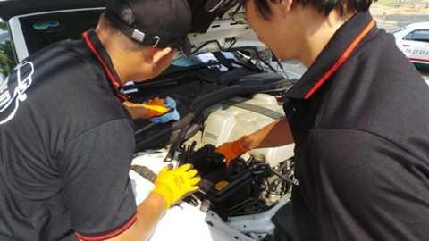 Các kỹ thuật viên thay nhớt miễn phí cho khách dự ngày hội Phong thái xe sang - Ảnh: H.Như