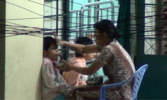 Bảo mẫu bạo hành trẻ nhiễm HIV trong bữa ăn - Ảnh trích từ clip của Ngọc Khải - Hải Hiếu