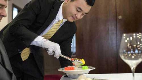Hu đang gắp những khối xếp hình nhựa giả làm thức ăn vào đĩa người huấn luyện. Ảnh: AFP