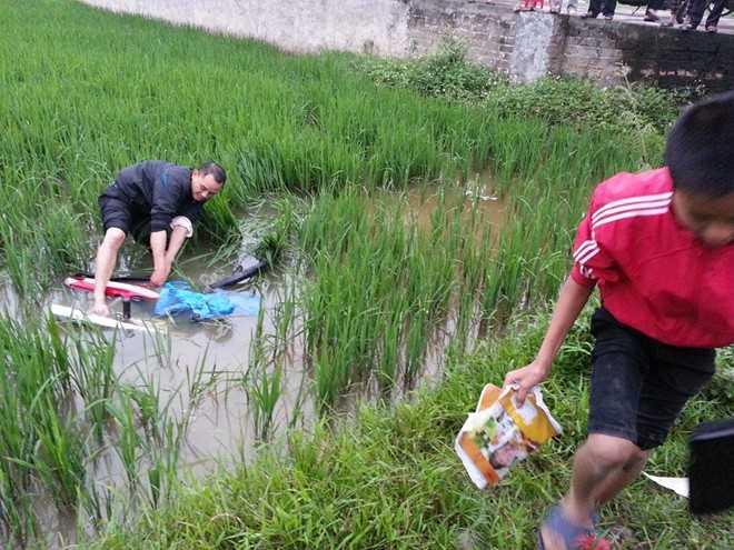 Xe máy hư hỏng nặng nằm dưới ruộng lúa. Ảnh: Tú Xuân.