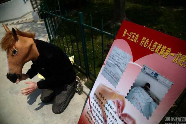 Người đàn ông 38 tuổi quỳ bên vỉa hè, đeo mặt nạ đầu ngựa để xin tiền chữa trị bệnh cho con