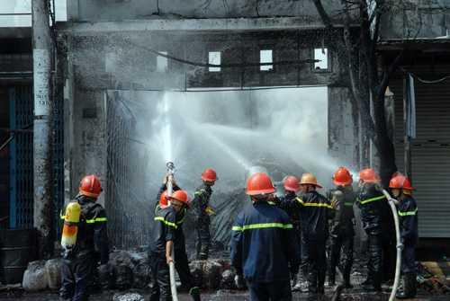 Cảnh sát cứu hỏa phun vòi rồng vào cửa hàng hóa chất. Ảnh: An Nhơn